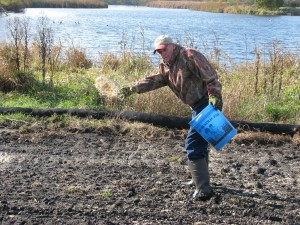 "Jack Hurst scatters prairie seeds on the wetland island in Warner Park. Thanks to Wild Warner, the area, used as the ""shooting island"" for Rhythm & Booms fireworks, will become a wetland area for wildlife. For the story, and more photos, click here to see our blog."